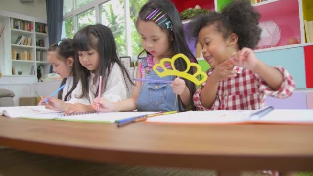 stockvideo's en b-roll-footage met groep van diversiteit kinderen spelen en tekenen foto op tafel in de thuisschool, kinderen diversiteit onderwijsconcept, internationale school, tilt up shot. - peuterklasleeftijd