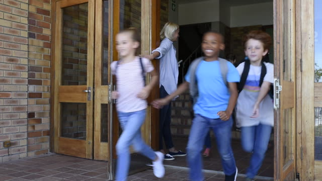 vidéos et rushes de groupe d'enfants de primaires extérieur de l'école en cours d'exécution - école