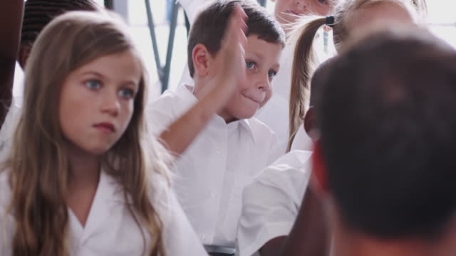 yerde oturan üniforma giyen ilköğretim öğrencileri grubu sınıfta soru cevaplamak için ellerini yükselt - üniforma stok videoları ve detay görüntü çekimi
