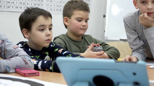 Group of elementary school children in classroom at lesson video