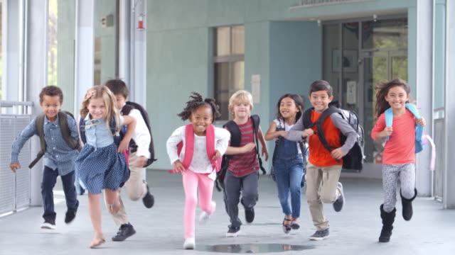Grupo de niños de escuela primaria corriendo en una escuela Corredor - vídeo