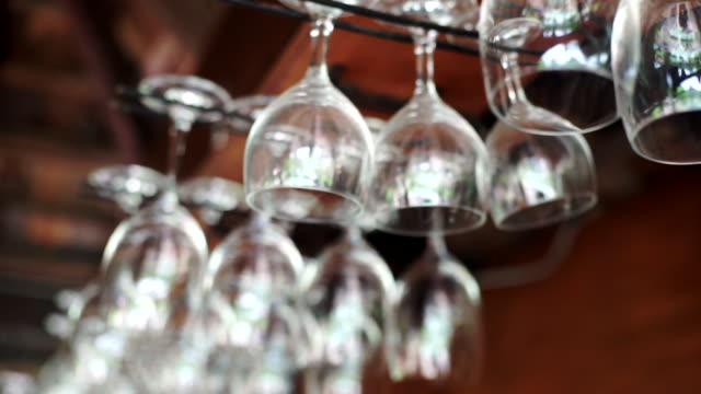 Group of empty wine glasses hanging above a bar rack.