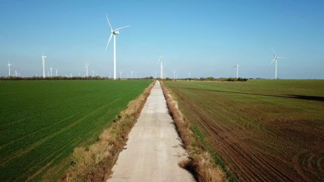 vídeos y material grabado en eventos de stock de grupo de ingenieros camina en contra del parque eólico - energía eólica