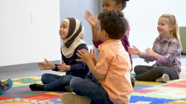 Group of ethnic kids in daycare An adorable group of children are sitting in their classroom. They are smiling and enjoying time with their teacher. child care stock videos & royalty-free footage