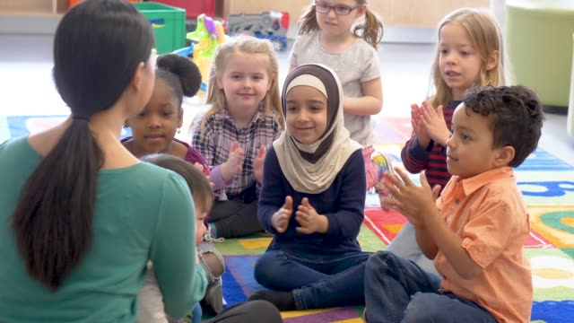 Group of ethnic kids in daycare An adorable group of children are sitting in their classroom. They are smiling and enjoying time with their teacher. elementary age stock videos & royalty-free footage
