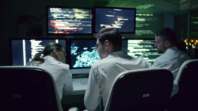 Group of Experts Discussing Cyber Security in Dark Office Rear view of three cyber security specialists talking at desk in front of multi-display workstation in dark IT office at night cybersecurity stock videos & royalty-free footage