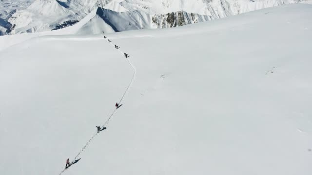 a group of extreme snowboarders   on the top of the mountain. freeride on off piste slope. top aerial  view. caucasus mountains, georgia, ski resort gudauri. - pościć filmów i materiałów b-roll