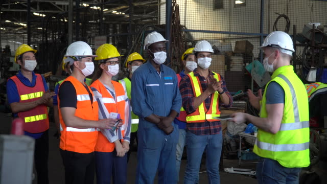 group of factory workers wear protective face mask meeting in industrial factory protect for pollution and coronavirus pandemic or covid 19 outbreak