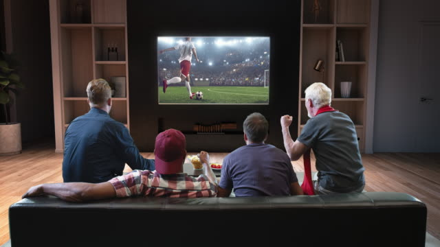 Group of fans are watching a soccer moment on the TV and celebrating a goal Group of fans are watching a soccer moment on the TV and celebrating a goal, sitting on the couch in the living room. The living room is made in 3D. match sport stock videos & royalty-free footage