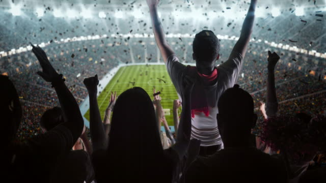 Group of fans cheering for sports team 4k video of a group of cheering fans watch a sport championship on professional soccer stadium. Their team wins and everybody are celebrating this event. People are dressed in casual cloth. Colourful confetti flies in the air. The stadium is made in 3D. match sport stock videos & royalty-free footage