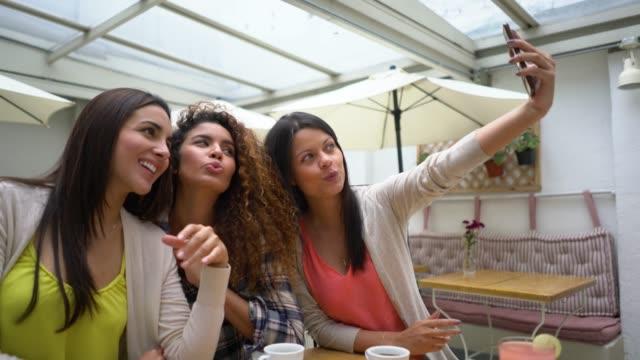 vídeos de stock, filmes e b-roll de grupo de amigas em um restaurante tomando um selfie e fazendo caretas - reunião encontro social