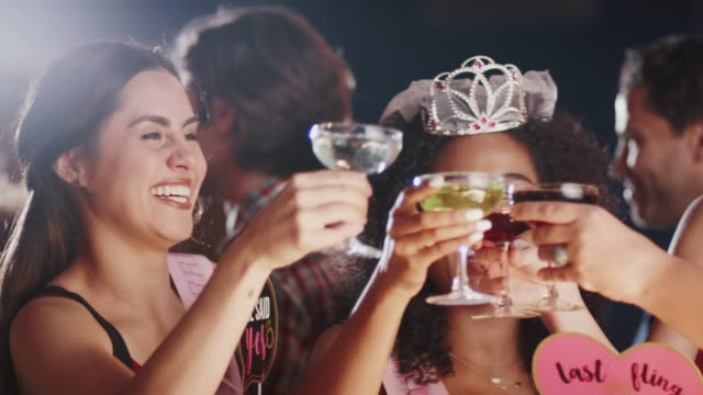 group of female friends celebrating with bride on hen party in bar - bachelorette party stock videos and b-roll footage