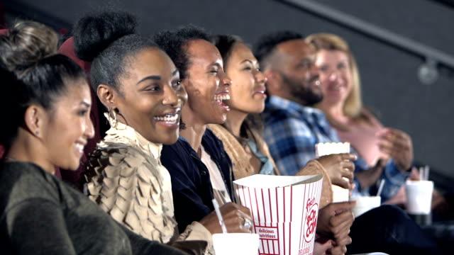 vidéos et rushes de groupe d'amis femmes appréciant le film ensemble - cinéma