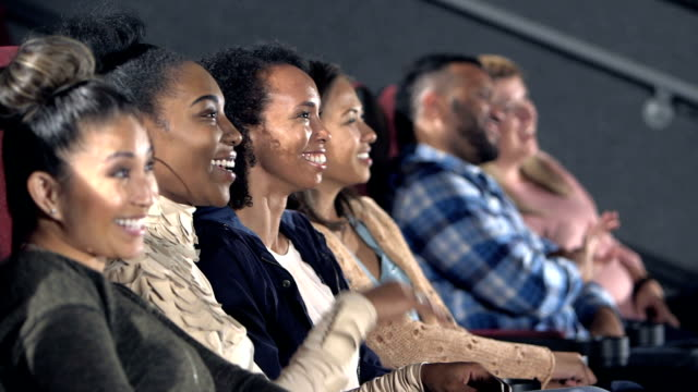 Group of female friends enjoying movie together A group of four multi-ethnic young and mid adult women watching a movie together at a movie theater, eating popcorn. They are smiling and laughing. performer stock videos & royalty-free footage