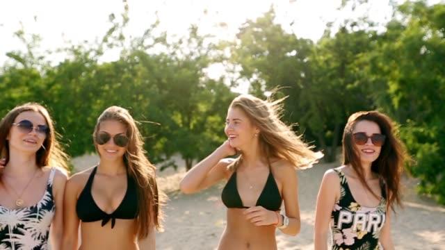 gruppe von freundinnen spaß zu fuß hinunter tropischen sandstrand an der kamera. frauen plaudern und lachen im sommer im freien. mädchen in bikini und badehose und badeanzug am meer - strandmode stock-videos und b-roll-filmmaterial