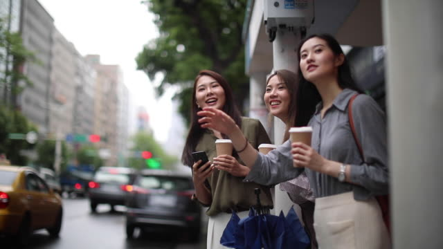 group of female friends looking for a taxi on rainy day - rideshare stock videos and b-roll footage