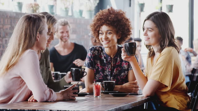 group of female friends meeting and sitting around table talking in cafe - shot in slow motion - bevanda calda video stock e b–roll