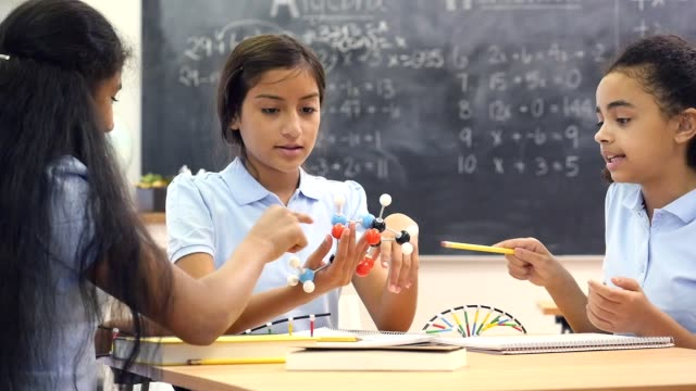Group of female junior high science lab partners discuss molecular structure video