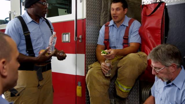 Grupo de bomberos de comer almorzar juntos - vídeo