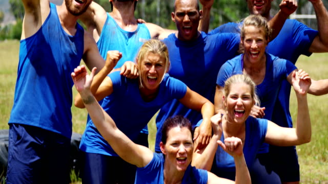 Group of fit people cheering together in boot camp 4k video