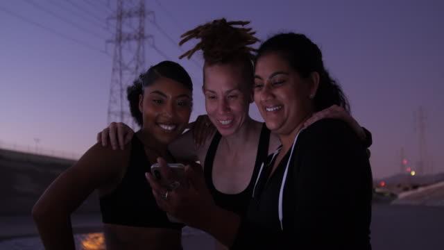 vídeos de stock e filmes b-roll de group of fitness women using mobile phone - amizade feminina