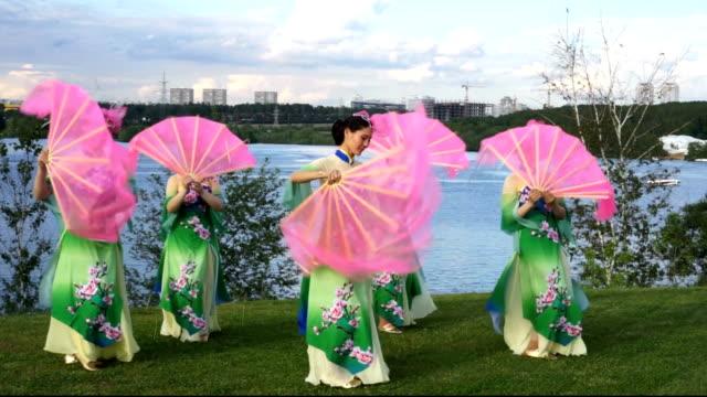 vídeos de stock, filmes e b-roll de grupo de cinco atrizes de mulheres asiáticas, em trajes chineses tradicionais com fãs dançando na beira da rio ao ar livre - tradição