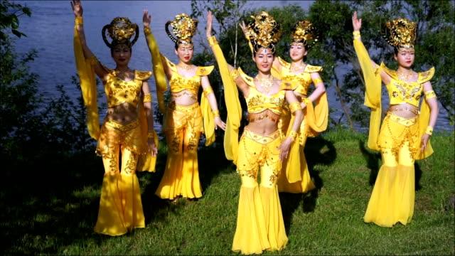 grupa pięciu azjatyckich kobiet aktorki w tradycyjnych chińskich żółtych strojach tańczących piękny taniec na brzegu rzeki - tradycja filmów i materiałów b-roll