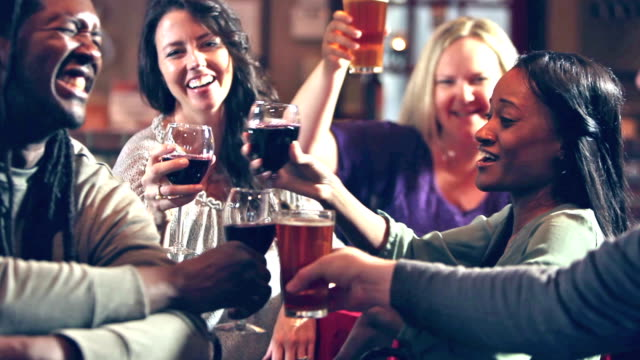 Group of five multi-ethnic people drinking in bar A group of five multi-ethnic people drinking beer and wine at a table in a bar restaurant. They are talking and smiling and then they raise their glasses for a toast. bar counter stock videos & royalty-free footage
