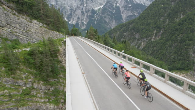 AERIAL Group of five road cyclists riding across a bridge high in the mountains