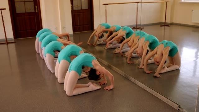 gruppe von flexiblen kleinen mädchen tun sich zurück strecken in einem tanz studio.ballet - ballettröckchen stock-videos und b-roll-filmmaterial