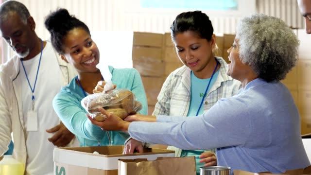 vídeos y material grabado en eventos de stock de grupo de voluntarios del banco de alimentos organiza donaciones de alimentos - food drive