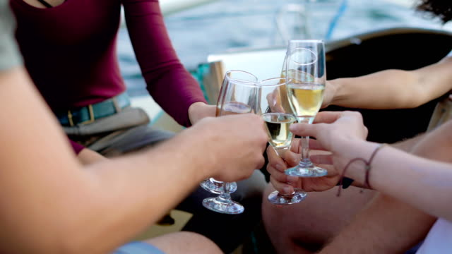 gruppe von vier freunden chillen auf einer yacht während segeln die meer geben reden und trinken champagner - champagner toasts stock-videos und b-roll-filmmaterial