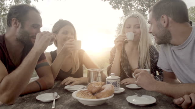 Group of four happy men and women friends smile, laugh and drink coffee during italian breakfast in natural rural scenic outdoor during summer sunny day morning in tuscany - slow-motion dolly HD video footage video