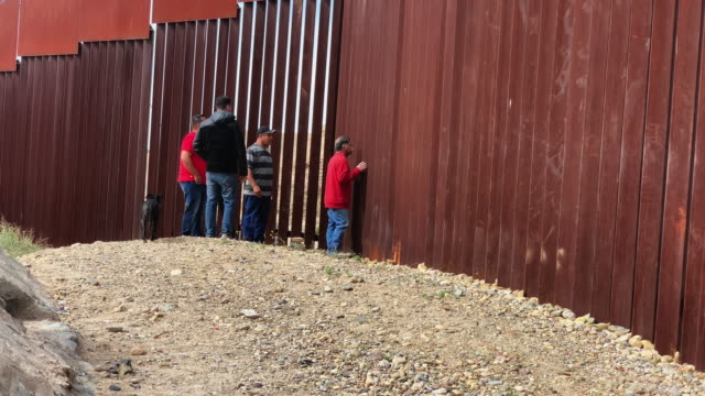 A Group Of Four Mexican Men Looking through the border Fence To The American Side, International Border Wall