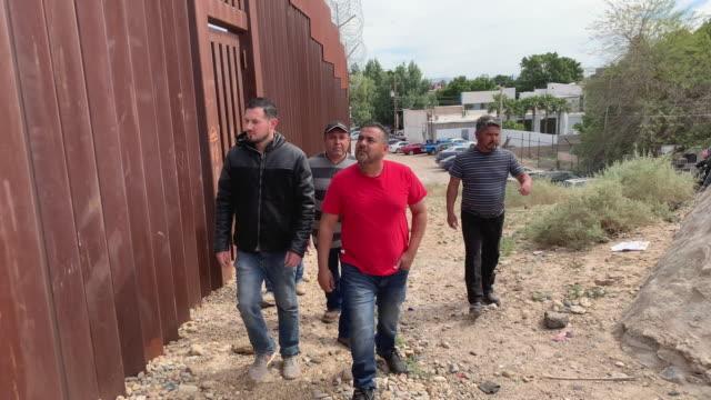 A Group Of Four Mexican Men Standing Near The Border Fence On The Mexico, Yuma Arizona Border