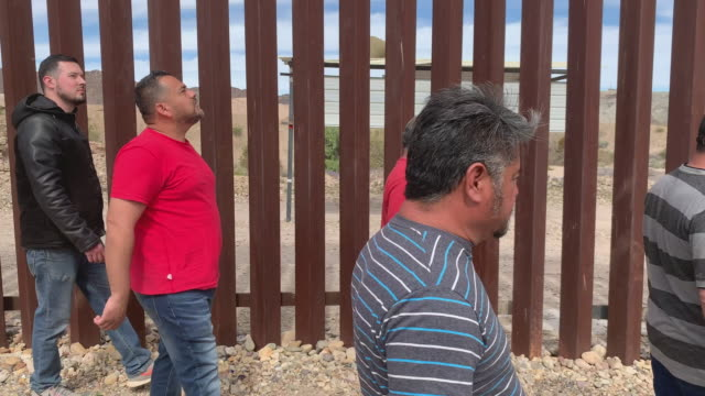 A Group Of Four Mexican Men Walking Near The Border Fence On The Mexico, Yuma Arizona Border