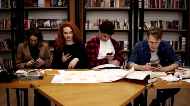 Gruppe von vier Studenten zwei Männer, zwei Frauen sitzen am Tisch zusammen in der Pause und mit Smartphones - SMS, Surfen im Internet, während sie in der Uni-Bibliothek zurück zu den Bücherregalen sitzen – Video