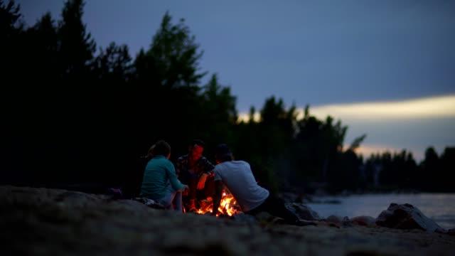 stockvideo's en b-roll-footage met groep van vier jonge reizende vrienden ontspannen door kampvuur op wilde zee strand 's nachts en het gebruik van stokken te houden brand branden - vier personen