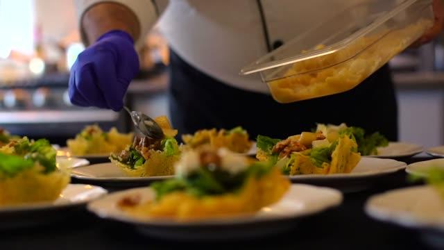 vidéos et rushes de groupe de assiettes de salade fraîche avec laitue et noix, sur une table à un grand banquet - banquet