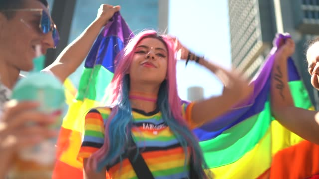 Group of friend waving a rainbow flag and having fun during LGBTQI parade Group of friend waving a rainbow flag and having fun during LGBTQI parade bisexuality stock videos & royalty-free footage