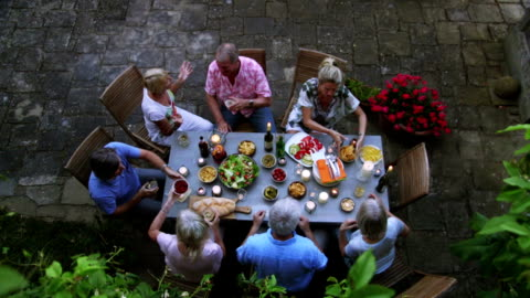 Group of Friends Al Fresco Dining A medium group of couples and friends are enjoying a meal outdoors, it is a lovely warm evening and they are all chatting and enjoying themselves. The footage has been taken in Tuscany, Italy. enjoyment stock videos & royalty-free footage
