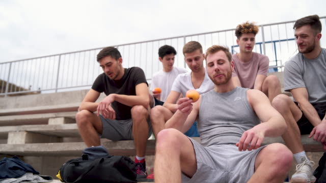 Group of friends are refreshing with fruits after amateur basket Group of young adults playing amateur basketball outdoor practice drill stock videos & royalty-free footage
