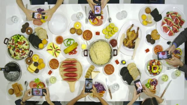 gruppe von freunden bei dinner-party mit allen menschen auf dem tisch verwendet ihr smartphone zum fotografieren von abendessen essen. instagram, soziales netzwerk sucht konzept. - teenage friends sharing food stock-videos und b-roll-filmmaterial