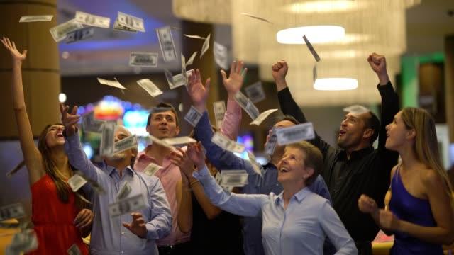 grupp vänner på casino firar en storvinst som kastar pengar till den luft som skrattar - spendera pengar bildbanksvideor och videomaterial från bakom kulisserna