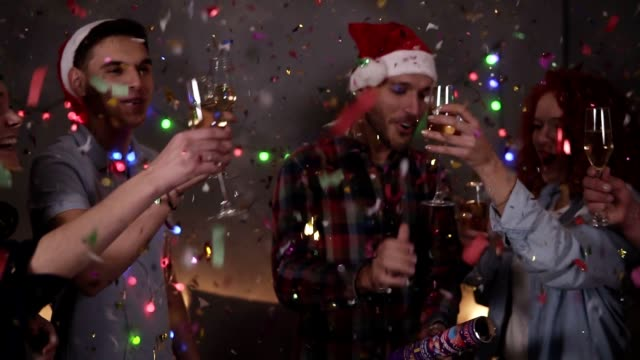Group of friends celebrating enjoying new years eve party having fun celebration. Friendly and joy. Happy emotion. Christmas decorations at home. Man exploding confetti stick, clinking glasses with champagne video