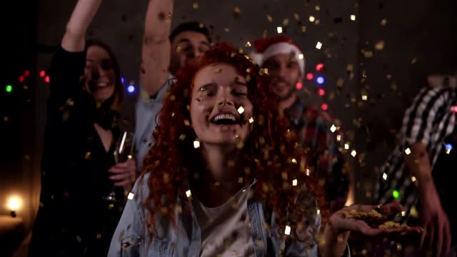 vídeos de stock e filmes b-roll de group of friends celebrating enjoying new years eve party having fun celebration. portrait of a curly red haired blowing glitter confetti from the hand then after friends throwing confetti on the background - new year