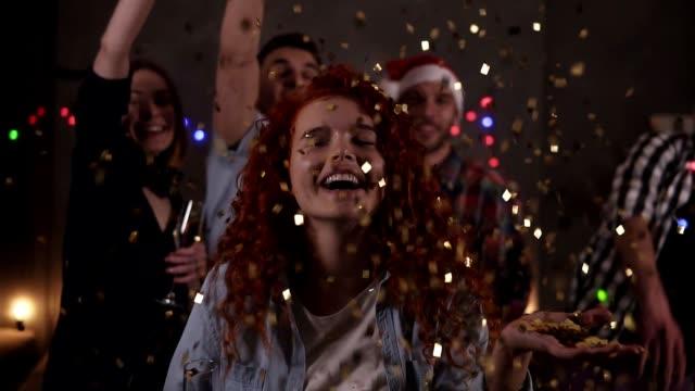 새해 전야 파티를 즐기는 축하 친구의 그룹은 즐거운 축하. 친구들이 배경에 색종이를 던진 후 손에서 반짝이는 색종이를 불고 있는 곱슬 머리의 초상화 - new year 스톡 비디오 및 b-롤 화면