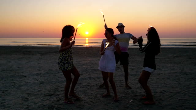 Group of friends celebrating with sparklers on the beach at sunrise video