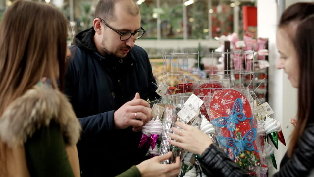 Group of friends chooses to buy toys and Christmas balls ornaments in a supermarket to decorate a Christmas tree