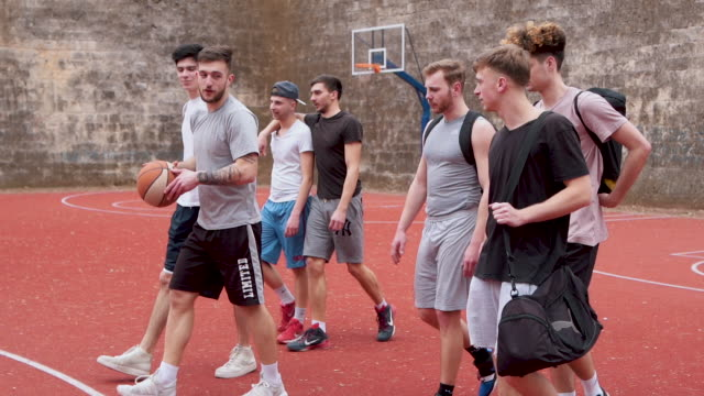 Group of friends coming to basketball court Group of young adults playing amateur basketball outdoor practice drill stock videos & royalty-free footage